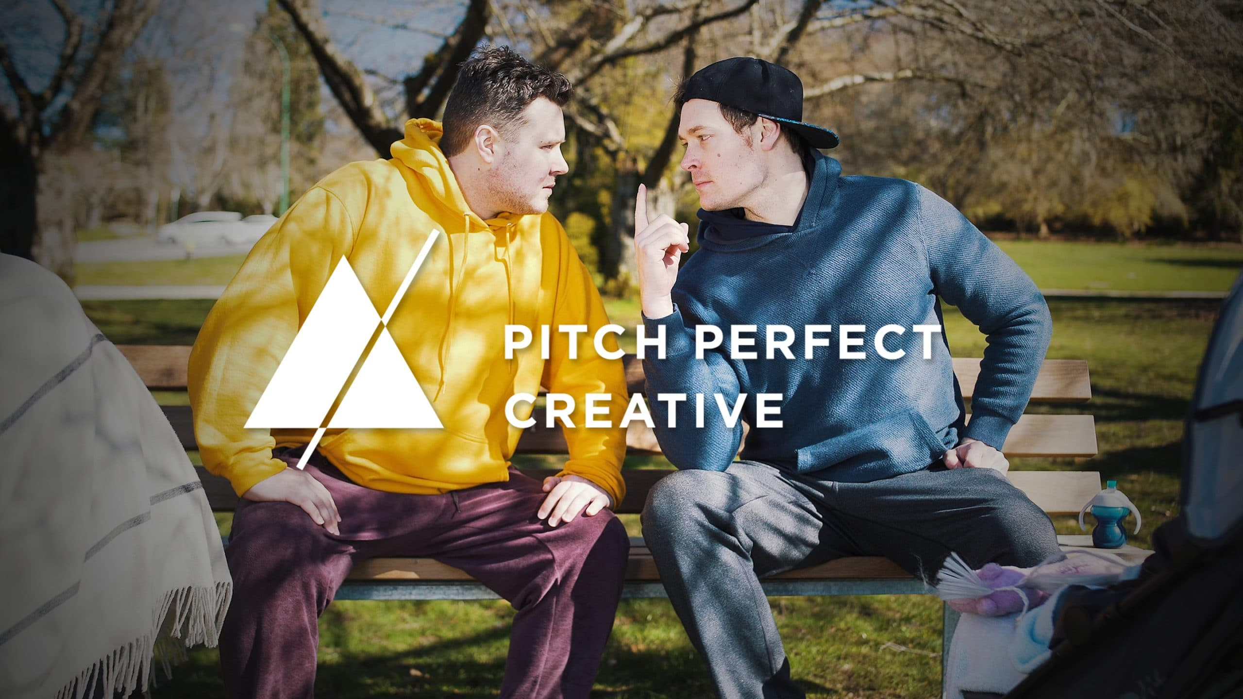 Two Dads sitting on a park bench. Logo says Pitch Perfect Creative