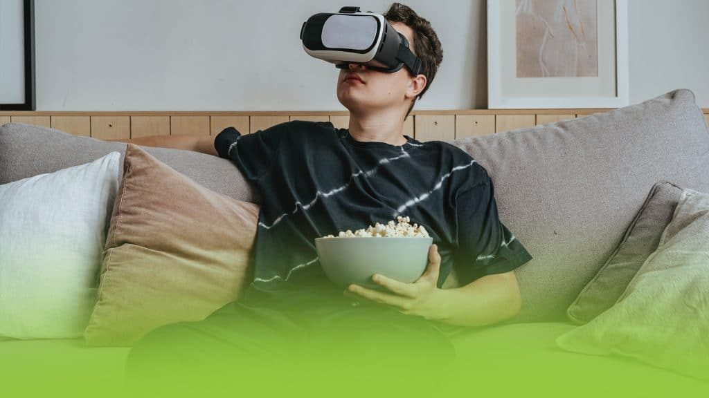 A young man with a bowl of popcorn, and a virtual reality goggles on.