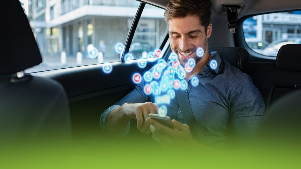 A handsome man in the back of a car using social media on his phone. Hearts and likes are exploding out of his phone.