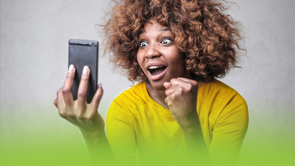 An exited woman watching a video on her phone in vertical mode.