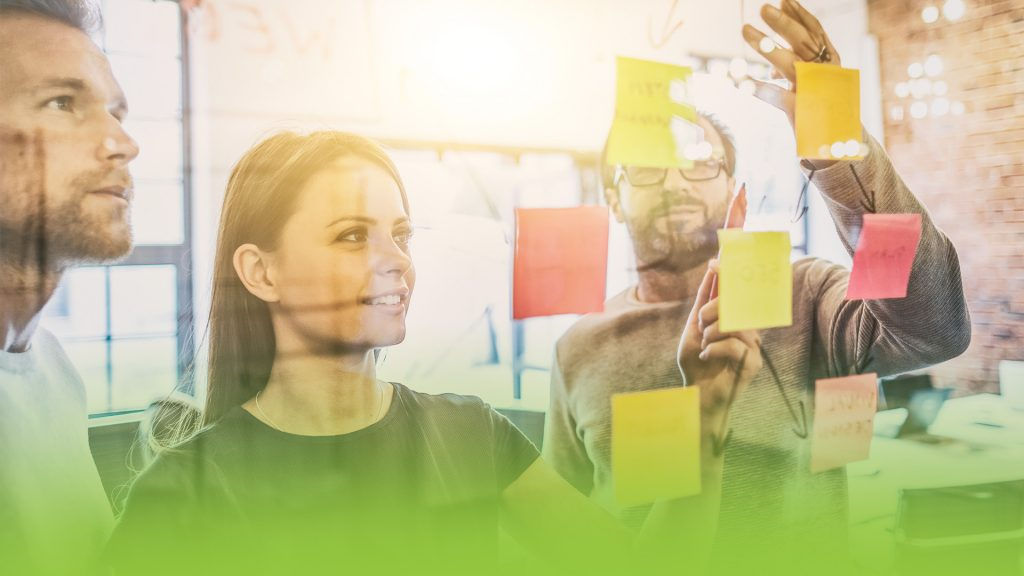 Three people reviewing sticky notes stuck to a wall of glass indoors. They are developing their video promotion strategy for their marketing.