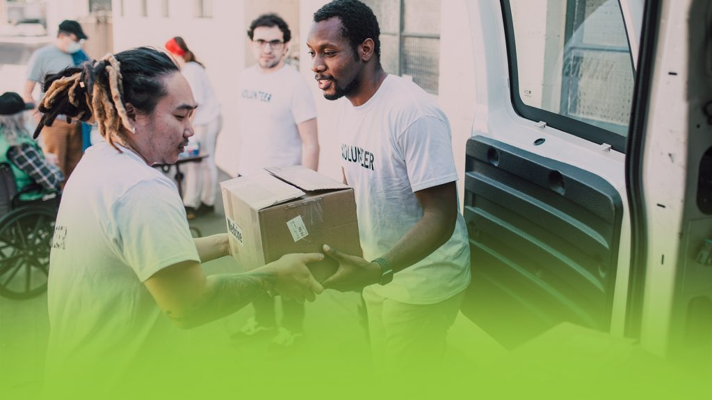Two men loading boxed supplies out of a van. They are volunteers for a nonprofit.
