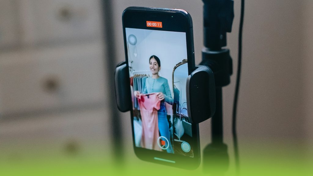 Close up of a smartphone. A woman is showing off clothes, while filming a TikTok video about fasion.