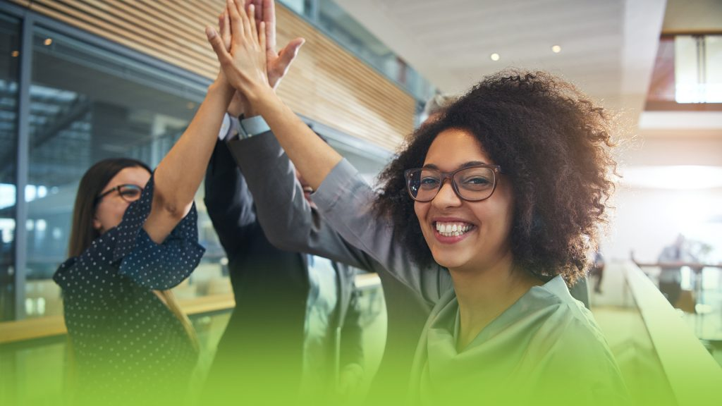 4 corporate work mates high fiving! They're happy because they have a great corporate video.