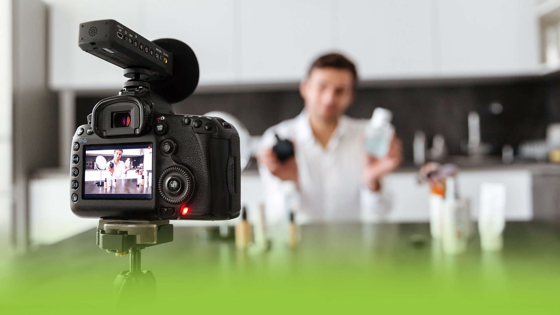 A man in a kitchen making a product video. His camera is recording and he's showing two skin care products.