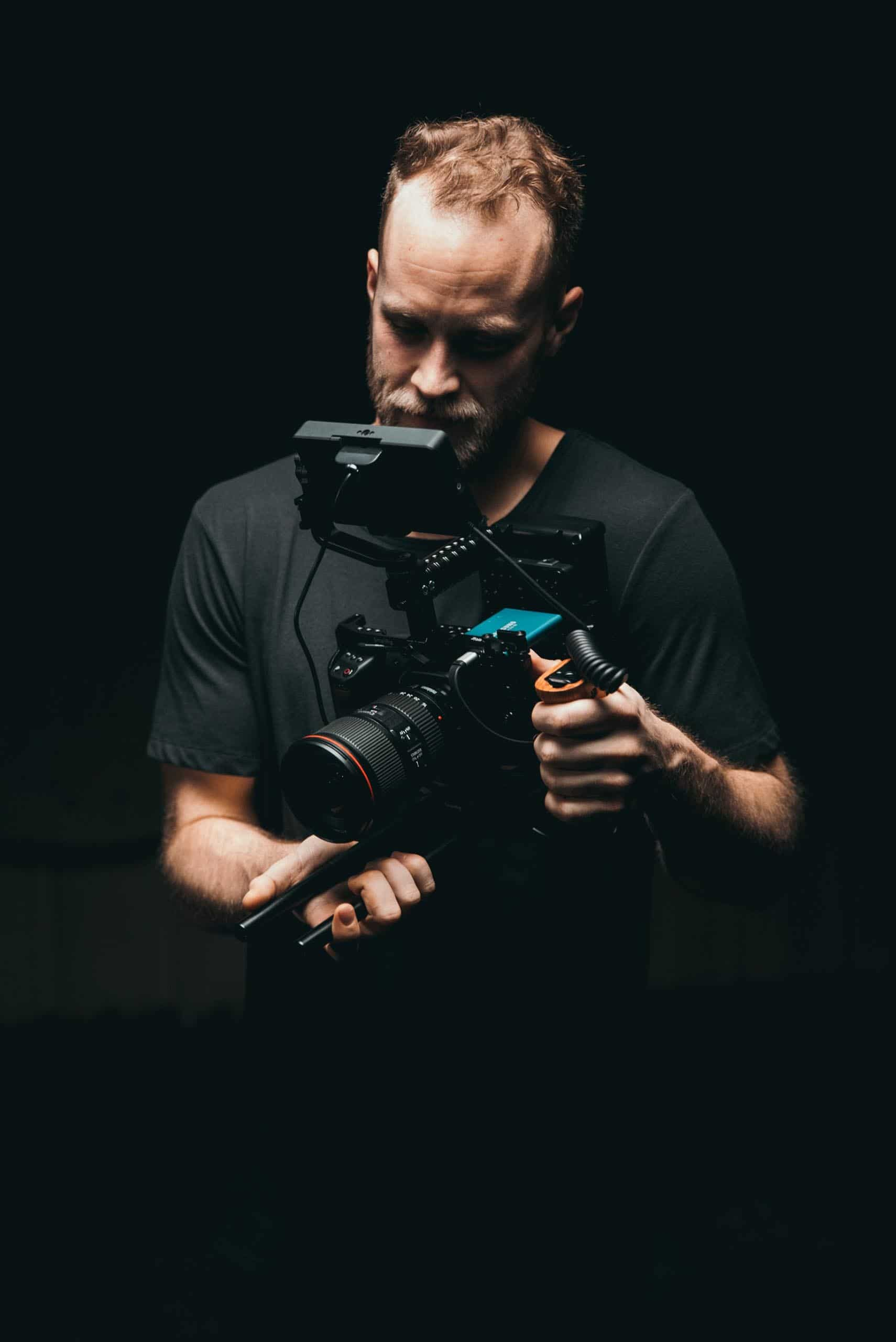 Middle aged man with a video production camera, standing by a black background.