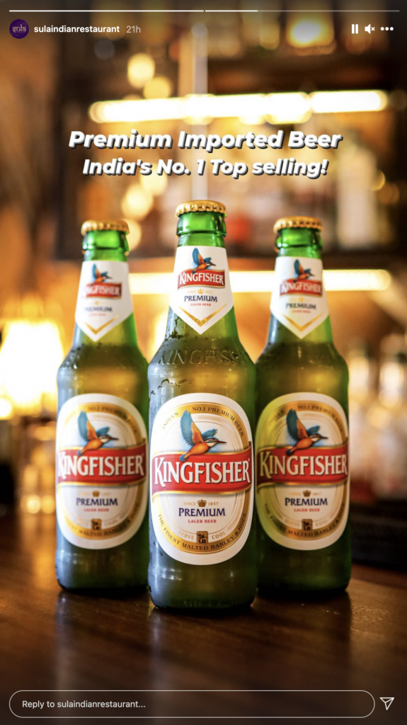 3 King fisher beers on a wooden counter.